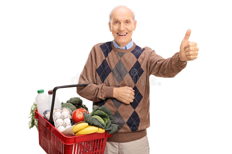 Senior holding a basket and giving thumb up. Senior holding a shopping basket full of groceries and giving a thumb up isolated on white background stock photography
