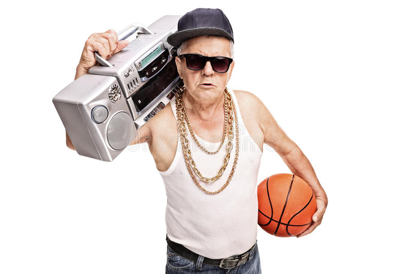 Senior holding a ghetto blaster and a basketball. Senior man in hip hop outfit holding a ghetto blaster and a basketball isolated on white background royalty free stock photo