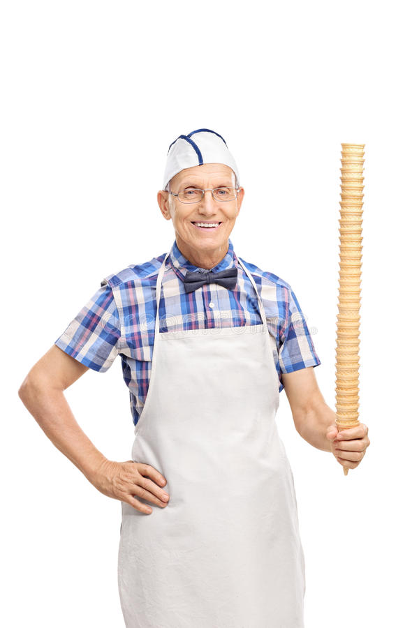 Senior holding a huge row of ice cream cones. Vertical shot of a senior with a white cap and apron holding a huge vertical row of ice cream cones and looking at royalty free stock photography