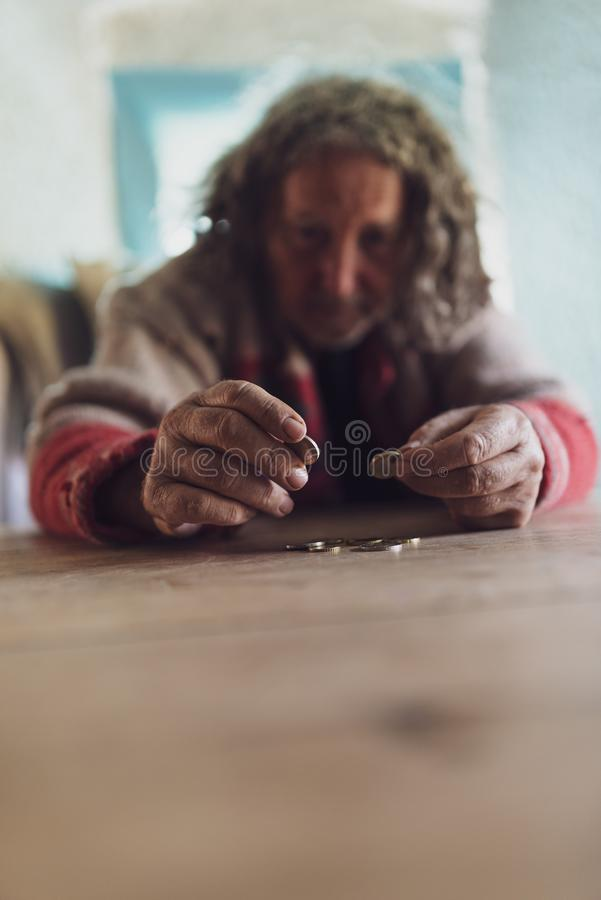 Senior homeless man with curly hair and torn sweater counting coins royalty free stock images