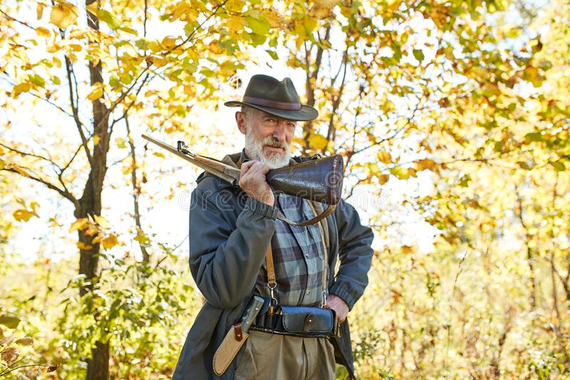 Senior hunter carry rifle gun on shoulder stock image