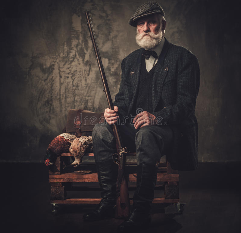 Senior hunter with a shotgun and pheasants in a traditional shooting clothing, sitting on a dark background. stock photo