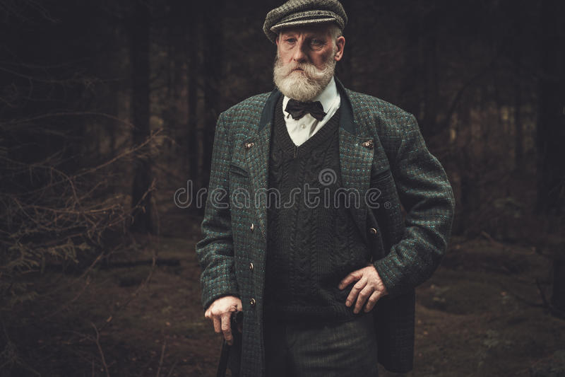 Senior hunter in a traditional shooting clothing, posing on a dark forest background. royalty free stock photos