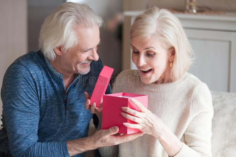 Senior husband presenting gift box to surprised beloved wife. Smiling senior husband making surprise giving gift box to amazed wife, happy aged woman get stock photo