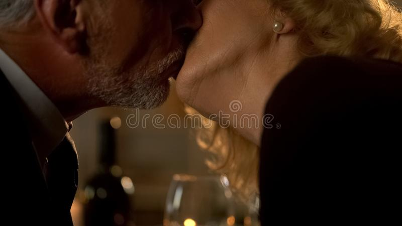 Senior husband and wife kissing during date in restaurant, aged couple in love stock image