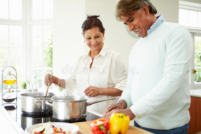 Senior Indian Couple Cooking Meal At Home. Happy Senior Indian Couple Cooking Meal At Home In Kitchen stock image