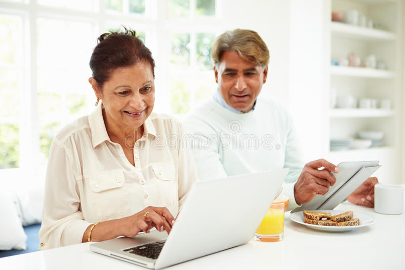 Senior Indian Couple Using Laptop And Digital Tablet At Home royalty free stock photo