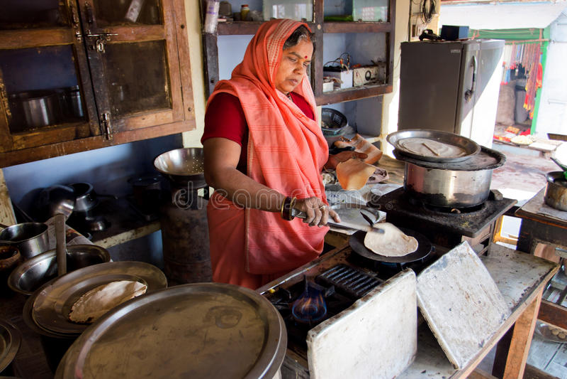 Senior indian lady in sari dress cooking stock photo