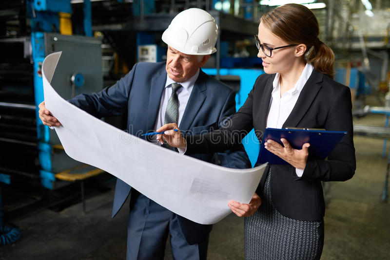Senior Inspector Proofing Factory Plans. Portrait of senior businessman looking at floor plans of modern factory with young assistant manager explaining the royalty free stock image