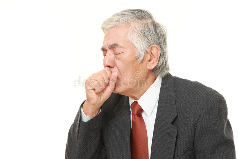 Senior Japanese businessman coughing. Studio shot of senior Japanese businessman on white background royalty free stock photography