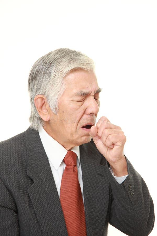 Senior Japanese businessman coughing. Studio shot of senior Japanese businessman on white background royalty free stock image