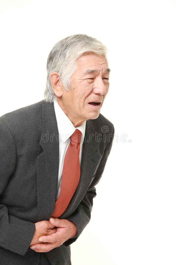 Senior Japanese businessman suffers from stomachache. Studio shot of senior Japanese businessman wearing a gray suit with dark red tie on white background stock photos