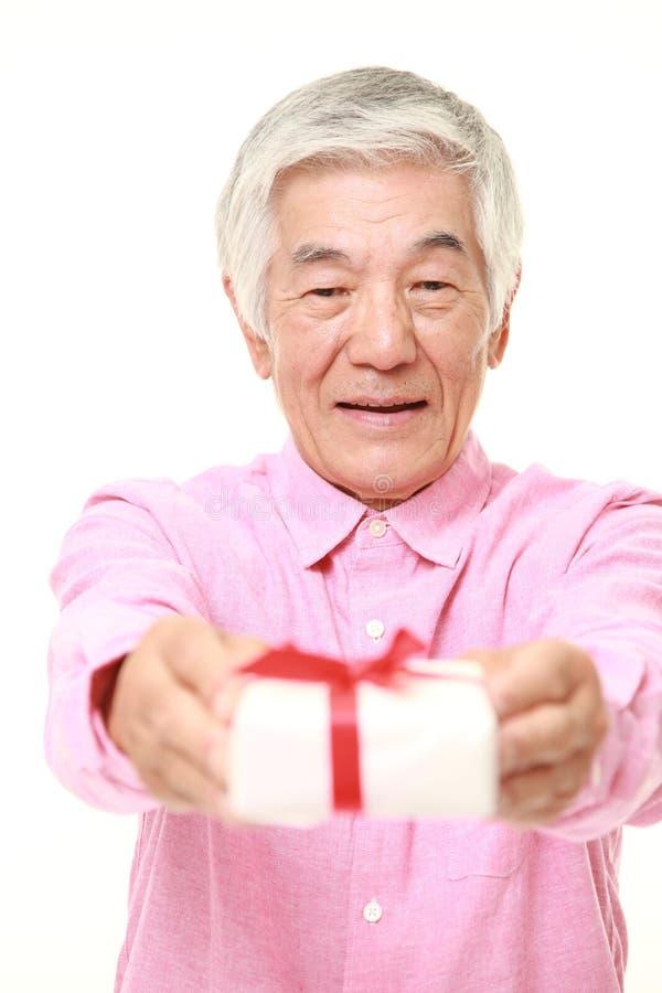 Senior Japanese man offering a gift. Studio shot of senior Japanese man on white background stock image