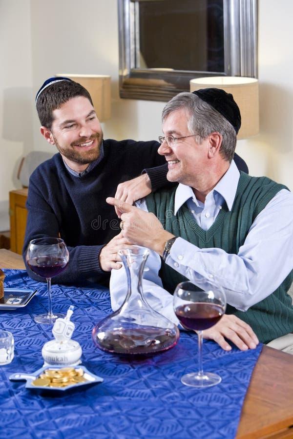 Senior Jewish man, adult son celebrating Hanukkah royalty free stock photography