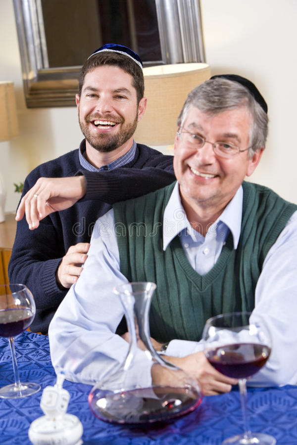 Senior Jewish man, adult son celebrating Hanukkah royalty free stock image