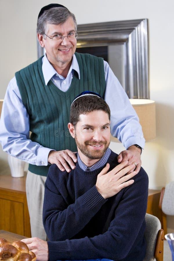 Senior Jewish man with adult son wearing yarmulkes stock image