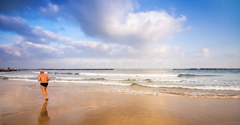 Senior jogging on the beach royalty free stock photography