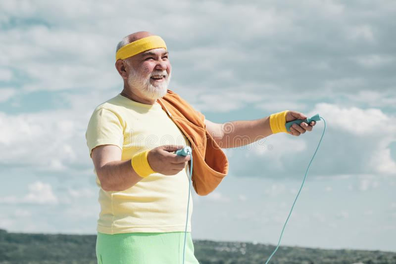 Senior jumping with skipping rope. Like sports. Freedom retirement concept. Active sport workout for old person. Senior. Sport man is doing sport outdoors royalty free stock photography