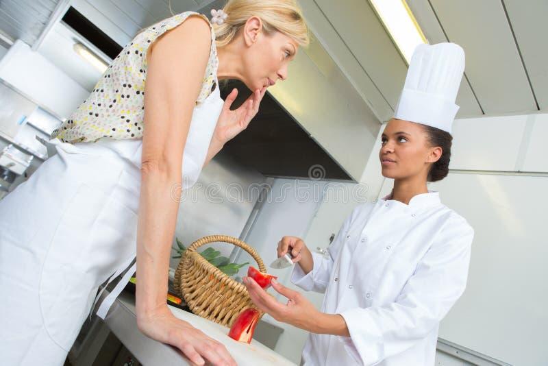 Senior and junior chefs in discussion stock photos