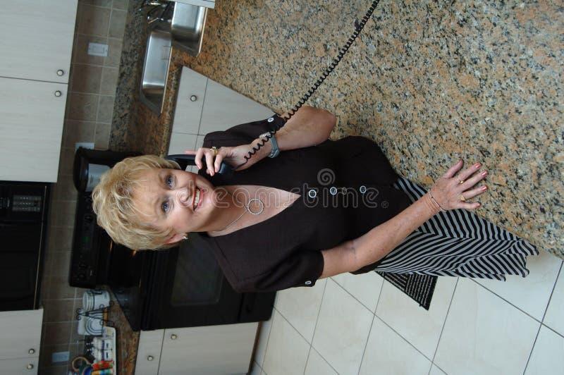 Senior in kitchen on phone stock photos