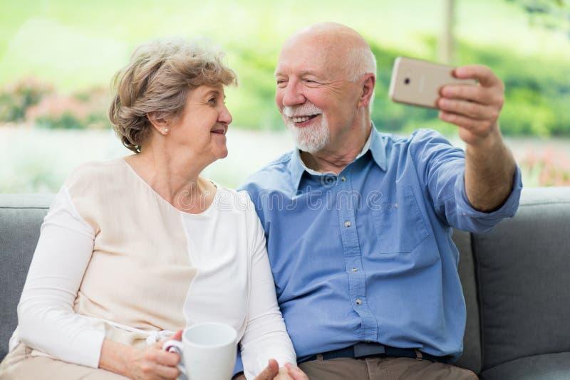 Senior koppels die thuis voor sociale media kiezen stock foto's