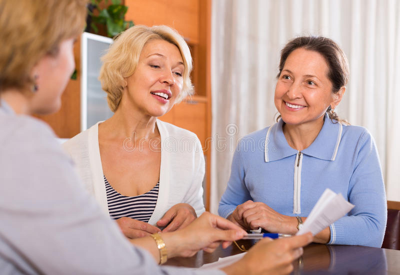 Senior ladies with agent. Happy senior ladies signing documents at bank with agent. Focus on blonde stock images