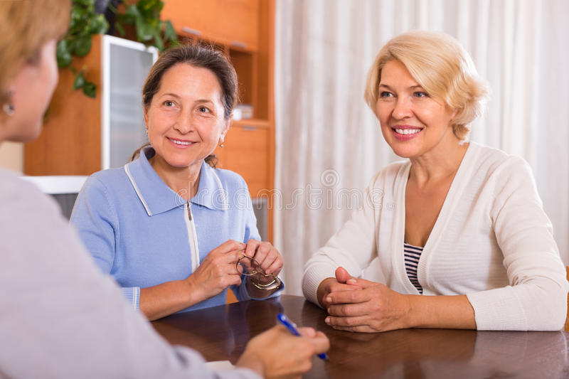 Senior ladies with agent. Senior ladies signing documents at bank and smiling. Focus on brunette royalty free stock image