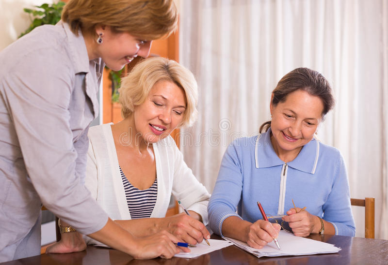 Senior ladies with agent. Two senior ladies signing documents at bank and smiling royalty free stock photography
