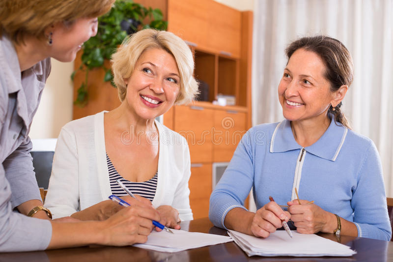 Senior ladies with agent. Two smiling senior ladies signing documents at bank royalty free stock image