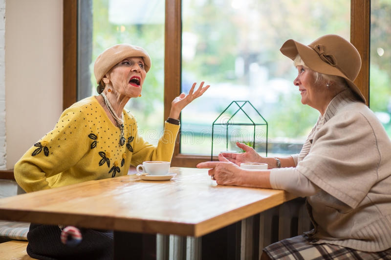 Senior ladies at cafe table. Women talking near window. The proud speech royalty free stock photography