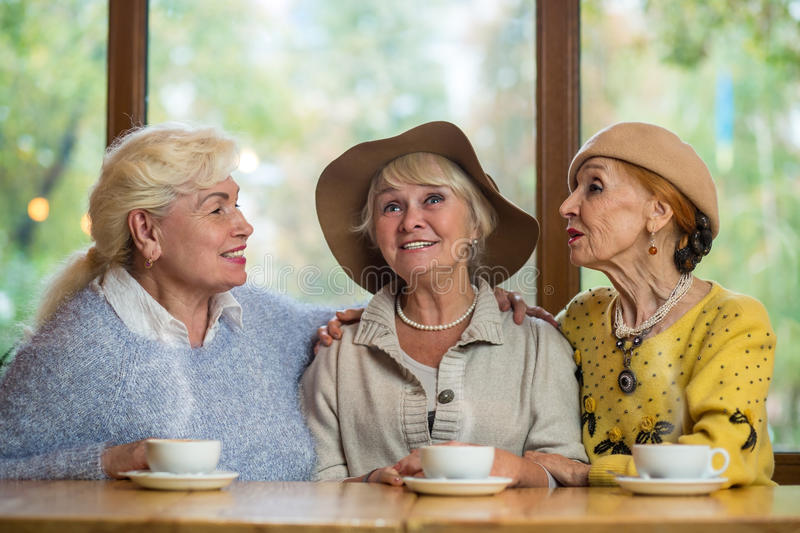 Senior ladies in a cafe. Women smiling and talking. Friendship is happiness royalty free stock photo