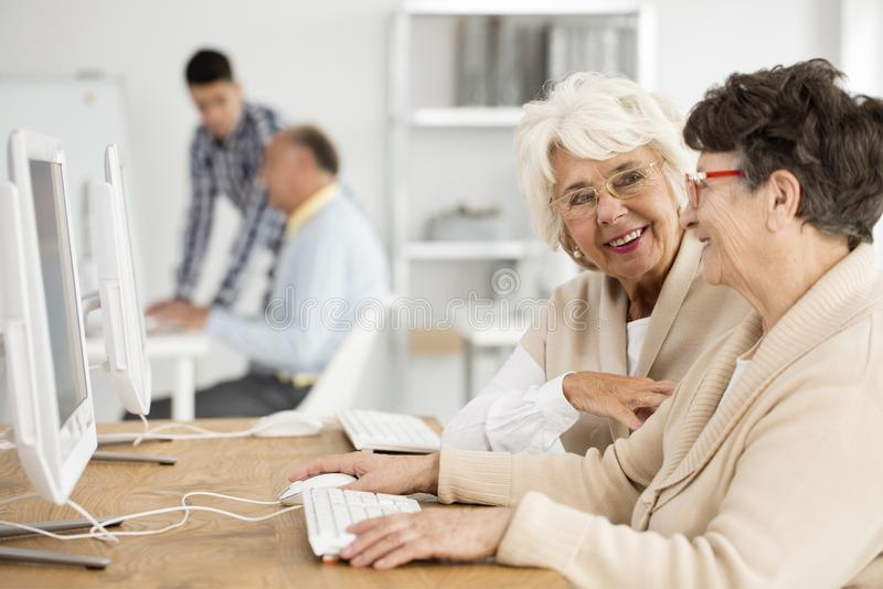 Senior ladies during IT classes. Two happy senior ladies talking during IT classes royalty free stock photography