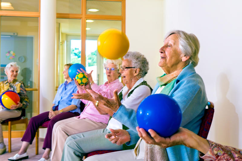 Senior ladies doing coordination exercises. Group of happy senior ladies doing coordination exercises in a seniors gym sitting in chairs throwing and catching stock images