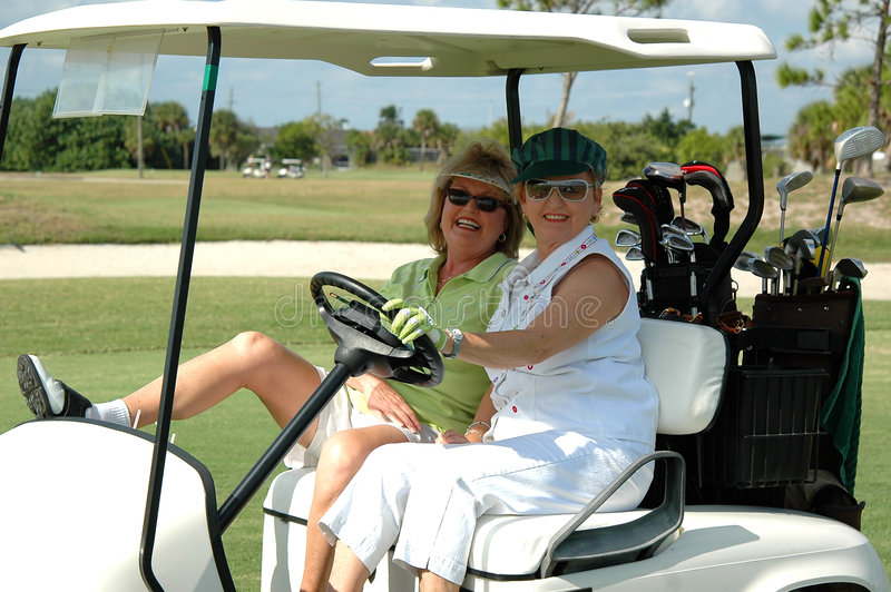 Senior ladies in golf cart. Two happy senior women in a golf cart royalty free stock photo
