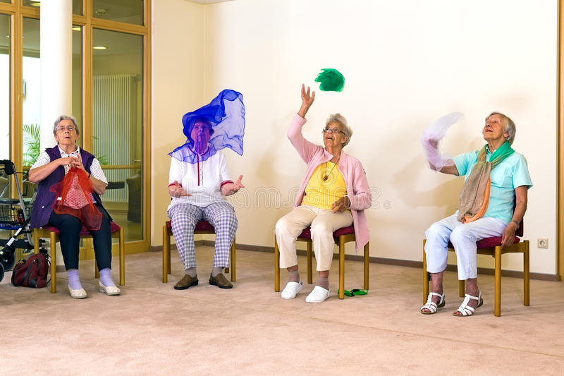 Senior ladies having fun while exercising. Senior ladies having fun while exercising at a seniors gym as they sit on chairs throwing colorful scarves in the air stock photos