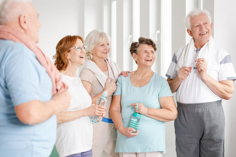Senior ladies holding bottles. Happy senior ladies smiling and holding bottles with water stock photo
