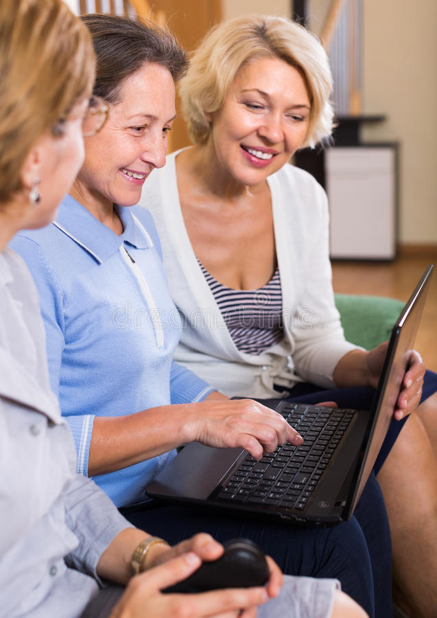Senior ladies with laptop. Happy smiling senior ladies on sofa with laptop buying something online. Focus on brunette royalty free stock photography