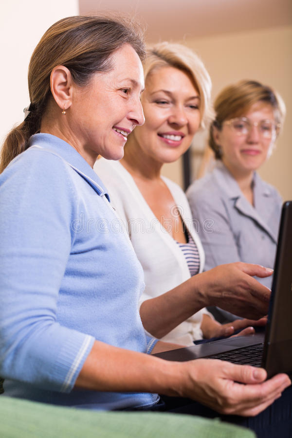 Senior ladies with laptop. Positive smiling senior ladies on sofa with laptop buying something online. Focus on brunette stock image