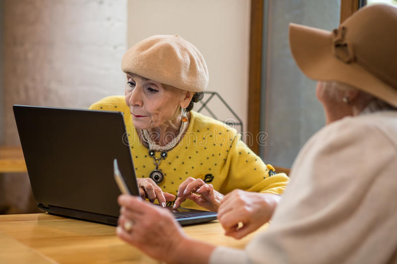 Senior ladies with laptop. Two old women indoor. Test the new software stock photography