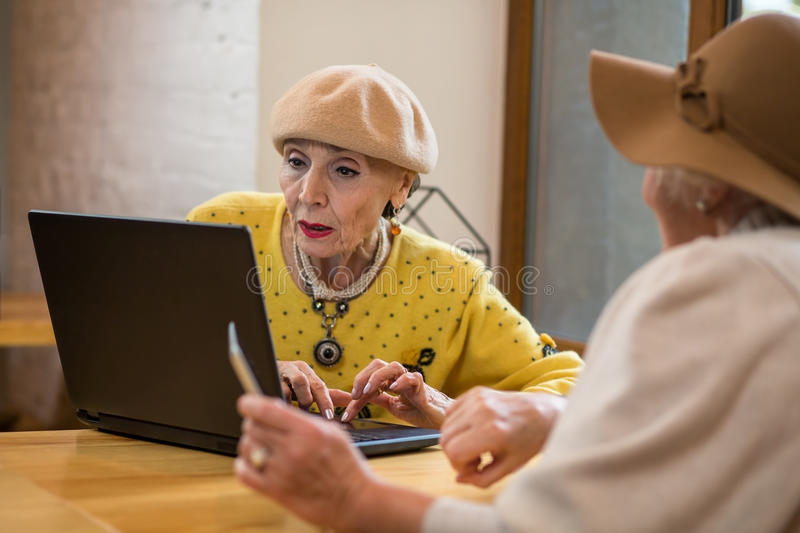 Senior ladies and laptop. Two old women indoors. Testing the touchpad royalty free stock image
