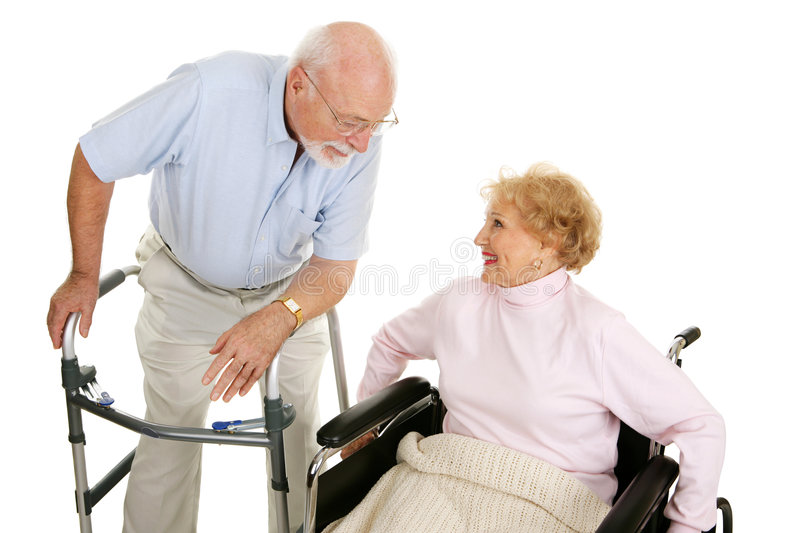 Senior Ladies Man. Senior man in walker flirting with a senior lady in a wheelchair. Isolated on white