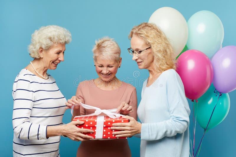 Senior ladies opening gift box together royalty free stock photos
