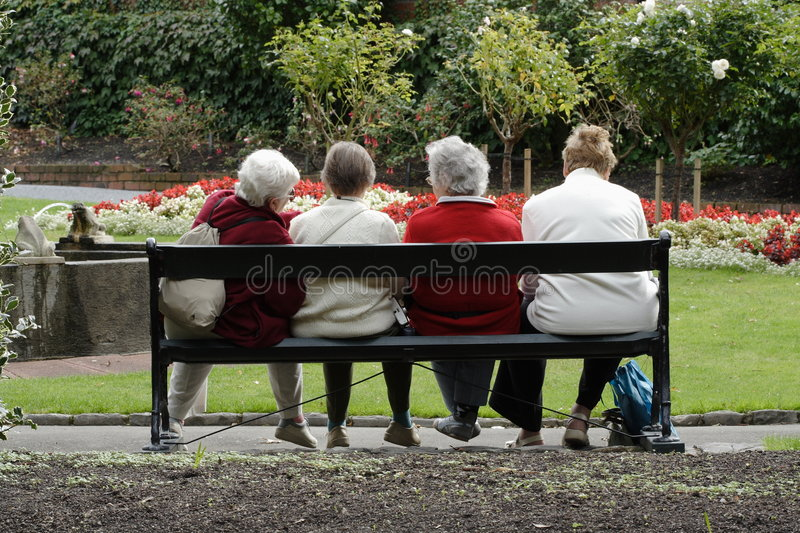 Senior ladies at the park. 4 old friends sitting on a park bench enjoying some friendly conversation royalty free stock image