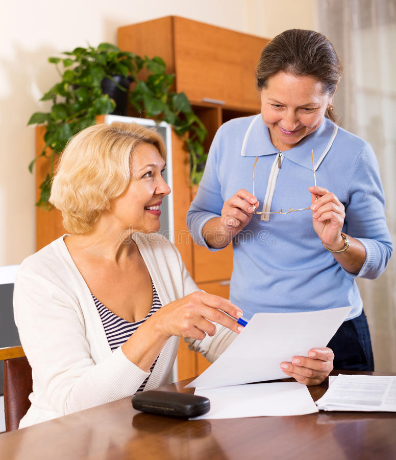 Senior ladies signing documents. Happy senior ladies signing documents at home. Focus on the women on the left royalty free stock images