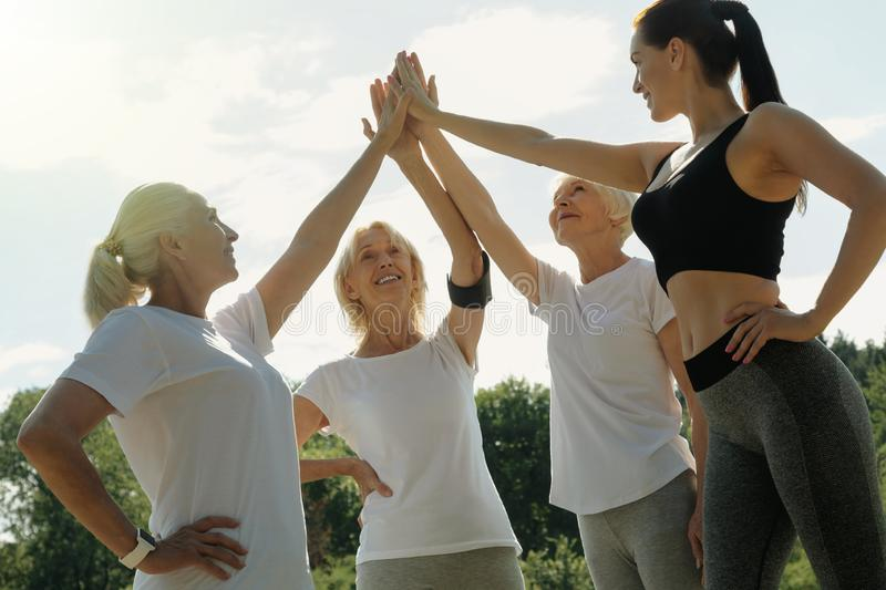 Senior ladies and their coach high fiving after workout royalty free stock images