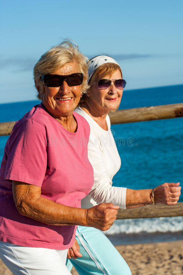 Senior ladies about to start jogging session. Portrait of friendly senior ladies in casual sportswear outdoors stock images