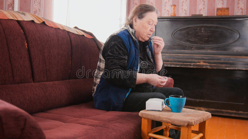 Senior lady - elderly woman at home takes the pills medication packages - pension healthcare royalty free stock photos