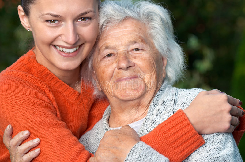 Senior lady and granddaughter. Young woman hugging her grandmother stock image