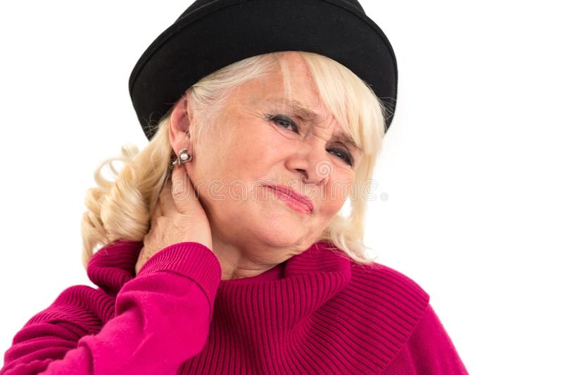 Senior lady has neck ache. Woman touching neck in pain. Problem caused by strained muscle royalty free stock image