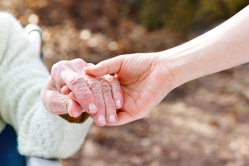 Senior Lady Holding Hands with Young Caretaker royalty free stock photography